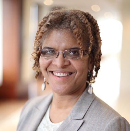A headshot of Ms. Cheryl D.S. Walker, Esq., in a grey blazer and glasses, smiling.